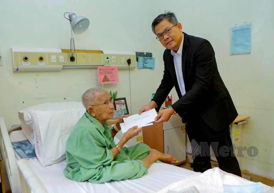 PENGURUS Besar MKH Berhad, Ahmad Yani menyampaikan sumbangan kepada Ujang ketika ditemui di Hospital Angkatan Tentera Tuanku Mizan, Wangsa Maju. FOTO Aizuddin Saad