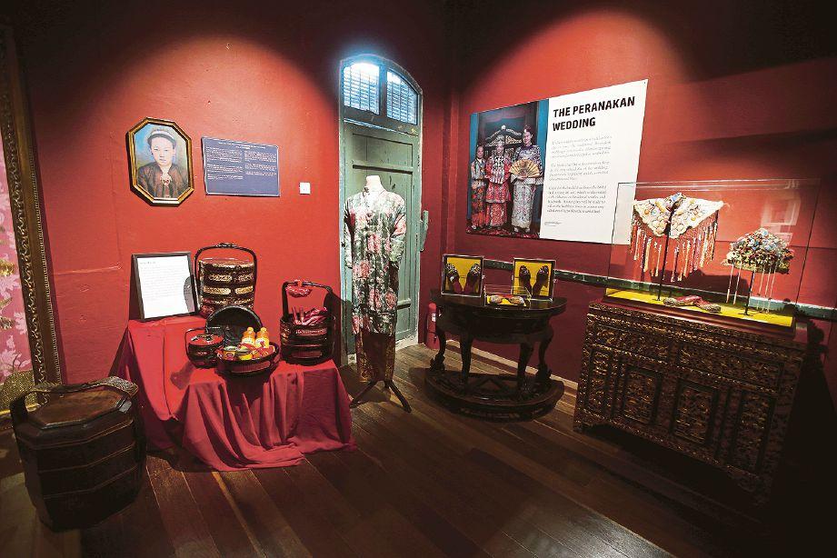PAKAIAN wanita dan barang kemas wanita Peranakan Cina yang dipamerkan.