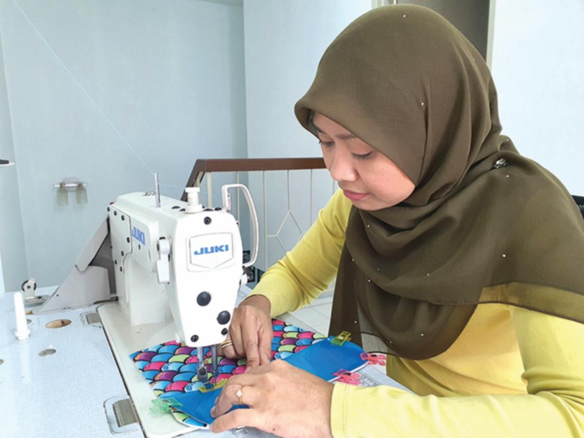 NOOR Syerifazidazetty menggunakan kemahiran menjahit untuk hasilkan pelbagai produk kraf tangan.