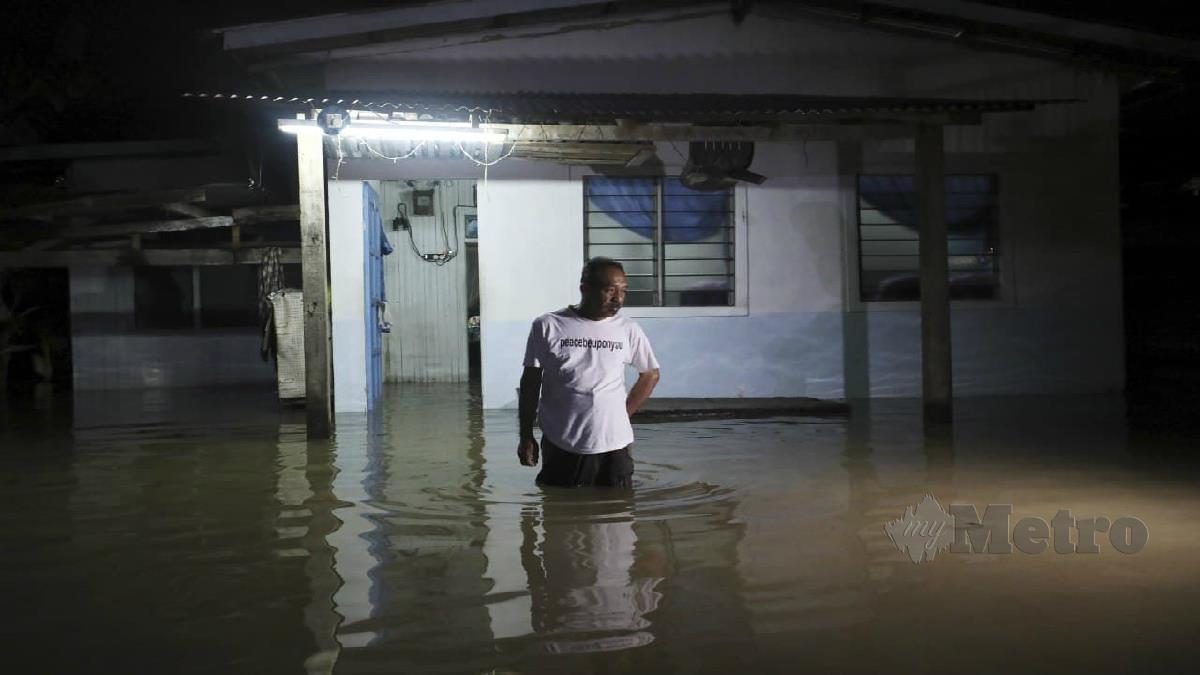 Penduduk berada di halaman rumahnya yang dinaiki air di Kampung Binjai Chendering malam ini. FOTO Ghazali Kori