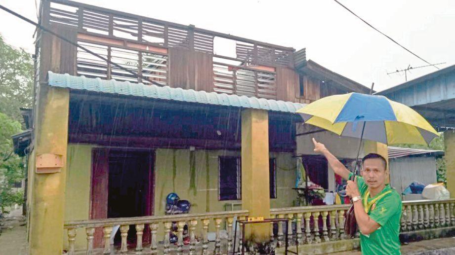 Zulkifli menunjukkan keadaan  rumahnya yang rosak  selepas dilanda ribut.