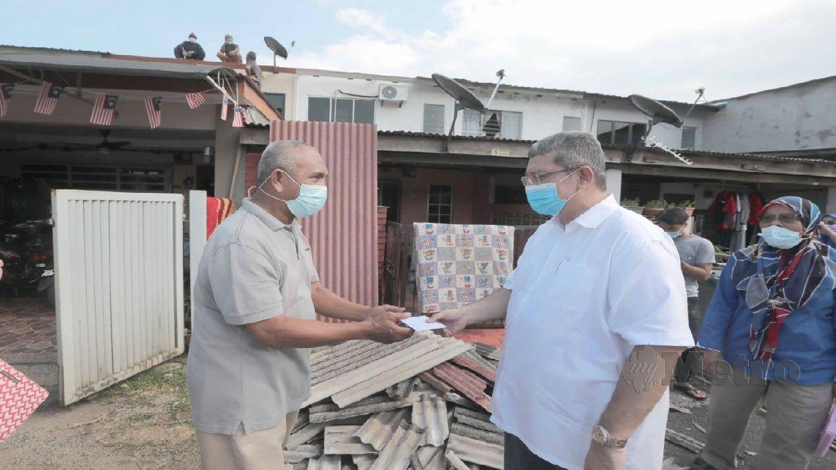 Saifuddin menyampaikan bantuan kepada Abdul Mubin selepas rumahnya mengalami kerosakan. FOTO Mohd Rafi Mamat