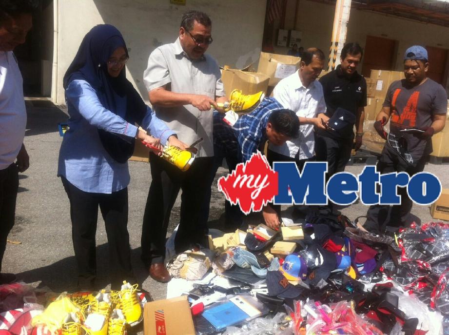 Ummi Nasrah (dua kiri) melupuskan barangan rampasan pada majlis pelupusan barangan kes di Kompleks Penyimpanan Bahagian Penguatkuasa KPDNKK Wilayah Persekutuan Kuala Lumpur. FOTO Nurul Hidayah Bahaudin
