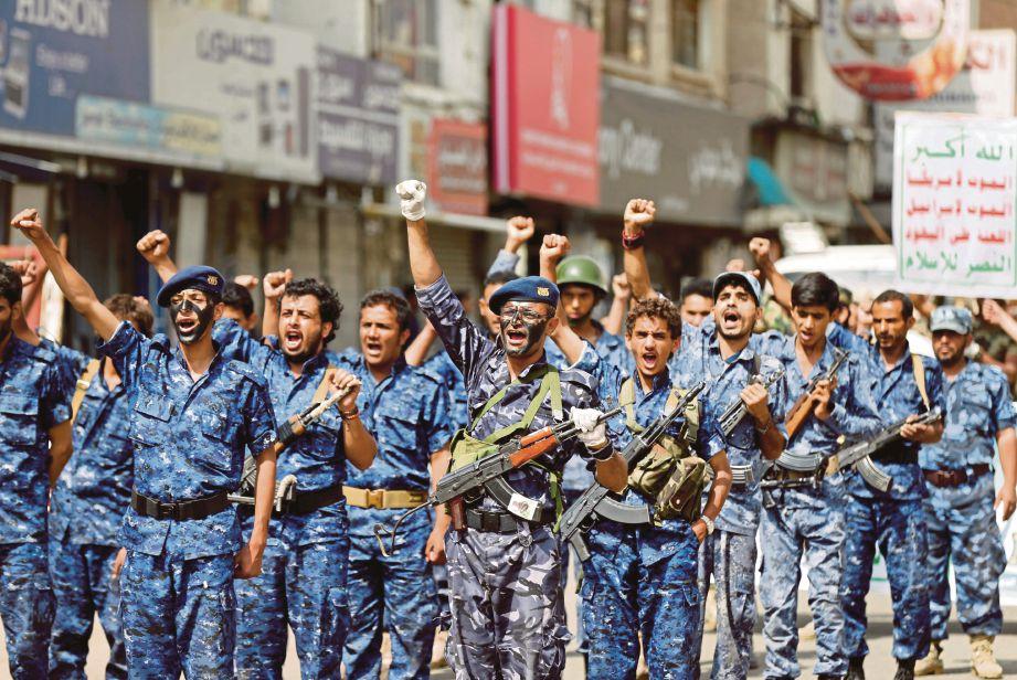 ANGGOTA pasukan keselamatan yang setia kepada pemberontak Houthi menyertai perarakan tentera di Dataran tahrir di Sanaa, semalam.  - Reuters