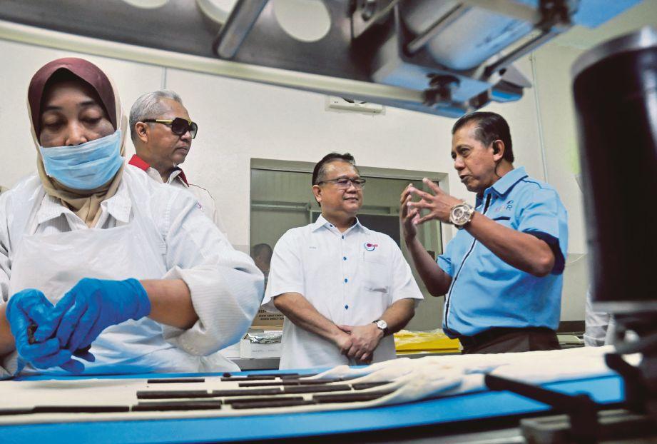 Alexander (dua kanan) dan  Annuar (dua kiri) mendengar penerangan  Pengarah Urusan Ezy Cakes, Daud Abu Bakar ketika melawat kilang pemprosesan makanan.