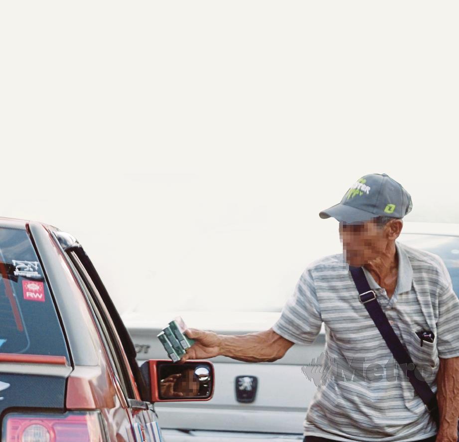 PENJUAL memberikan rokok yang dijual kepada pelanggan di Jalan Pasar, Kuantan.
