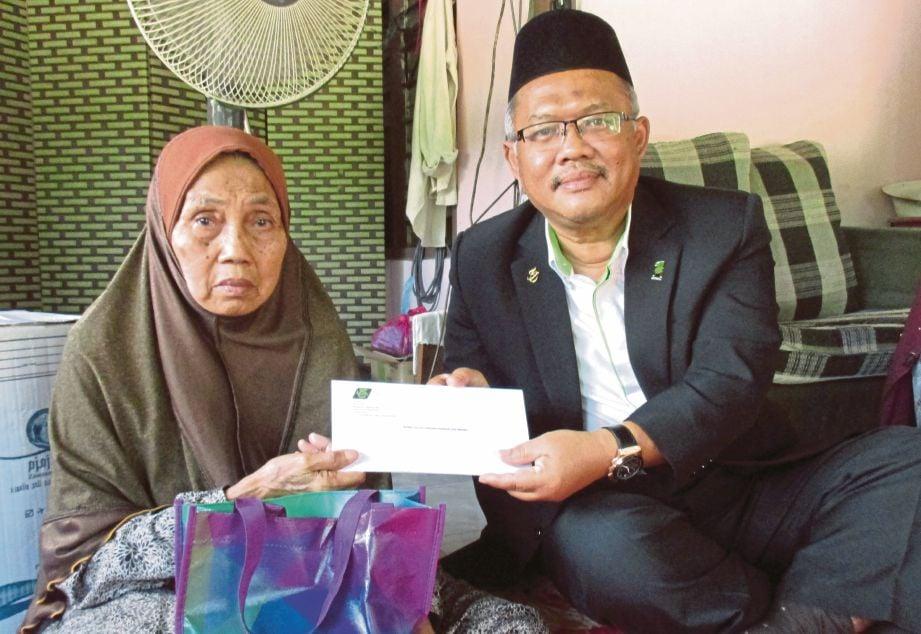 JOHARI  menyampaikan sumbangan  kepada Samsiah di rumahnya di Parit 1/7, Labu Kubong, Chenderong Balai, semalam.