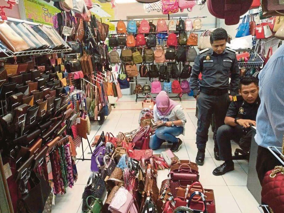 ANGGOTA KPDNKK merampas beg tiruan ketika serbuan di Seksyen 14, Shah Alam.