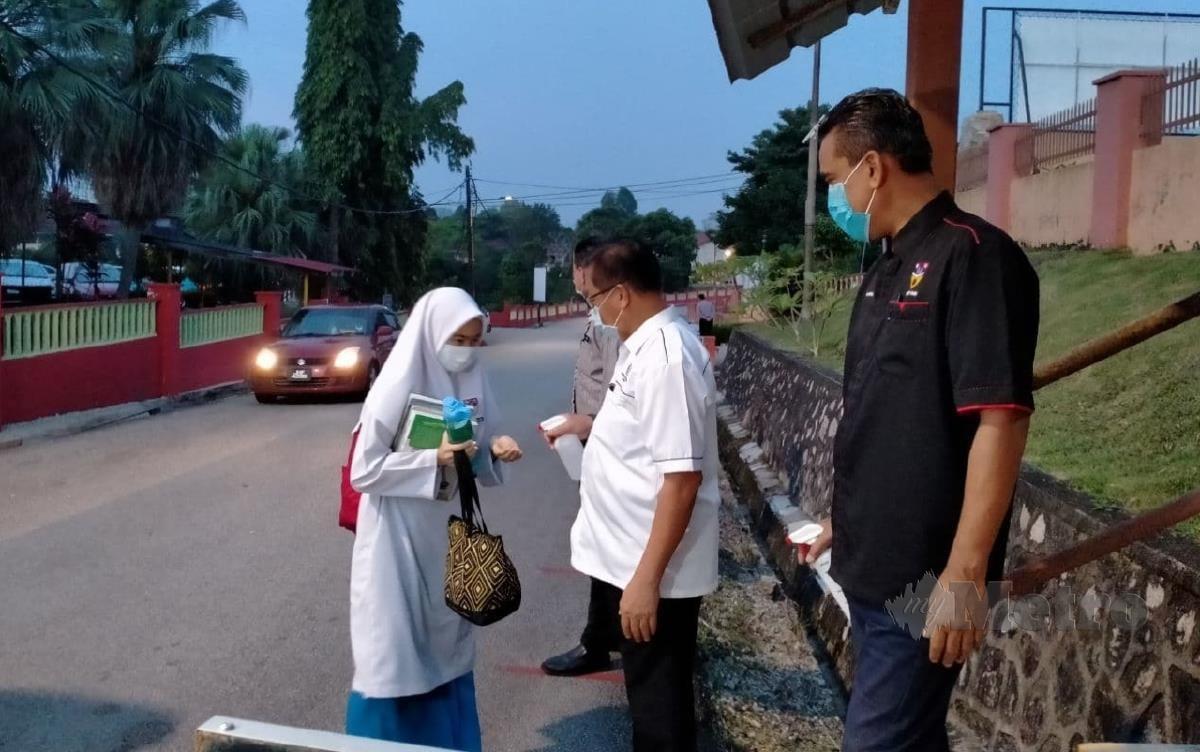 PELAJAR SMK Sultan Ismail diperiksa suhu badan dan diberi pensanitasi tangan sebelum memasuki sekolah. FOTO Omar Ahmad.
