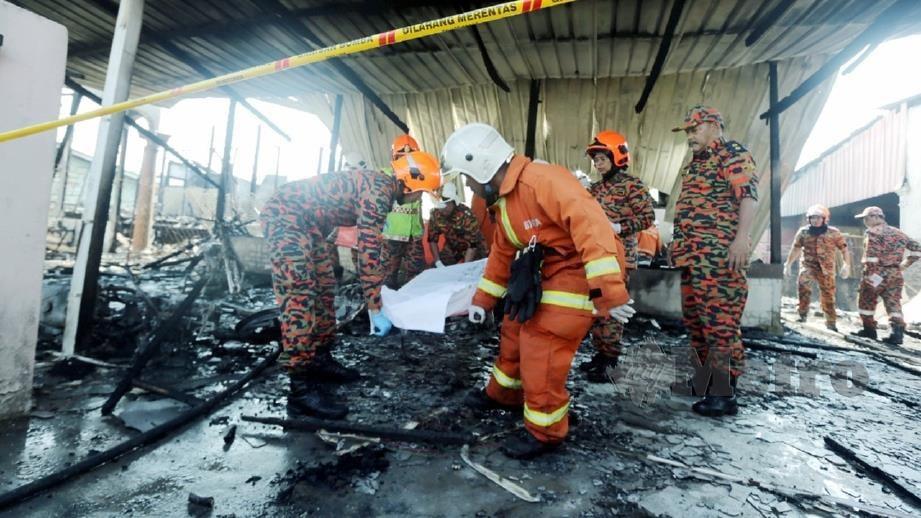 ANGGOTA Bomba dan Penyelamat mengusung jenazah tiga beranak yang meninggal dunia dalam kebakaran. FOTO Zulkepli Osman
