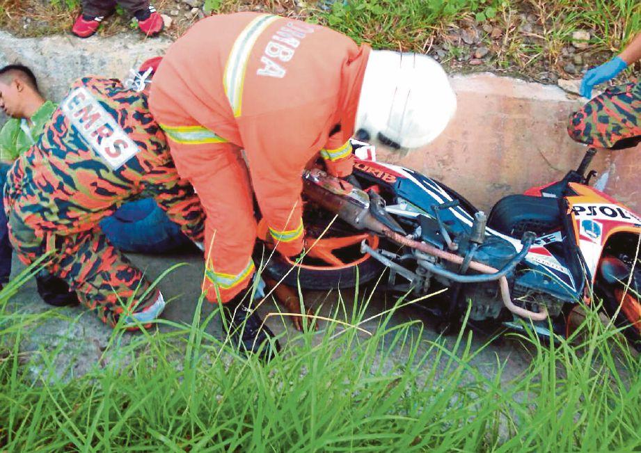 ANGGOTA  bomba membantu mengalihkan motosikal yang menindih   mangsa di tempat kejadian.