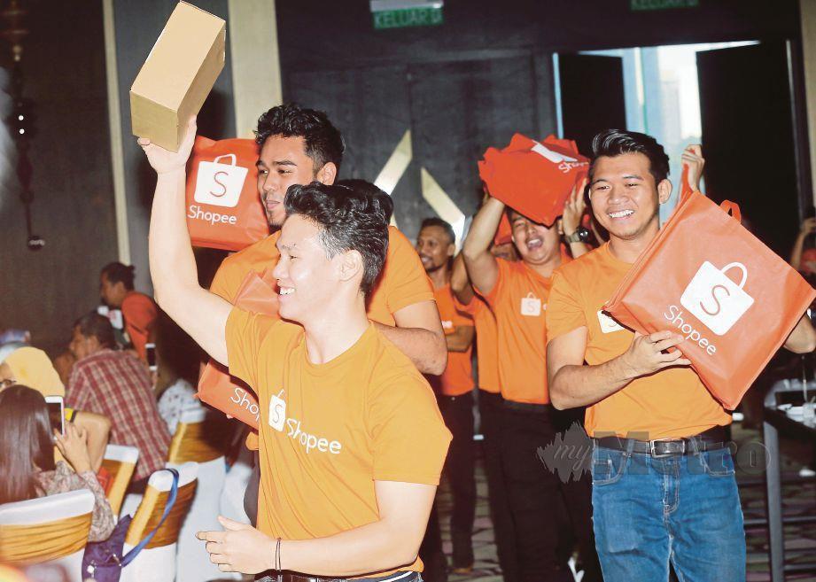 KAKITANGAN Shopee mengedar gooddies untuk tetamu pada pelancaran Shopee24 dan kempen Shopee 7.7 Orange Madness, semalam. FOTO Owee Ah Chun