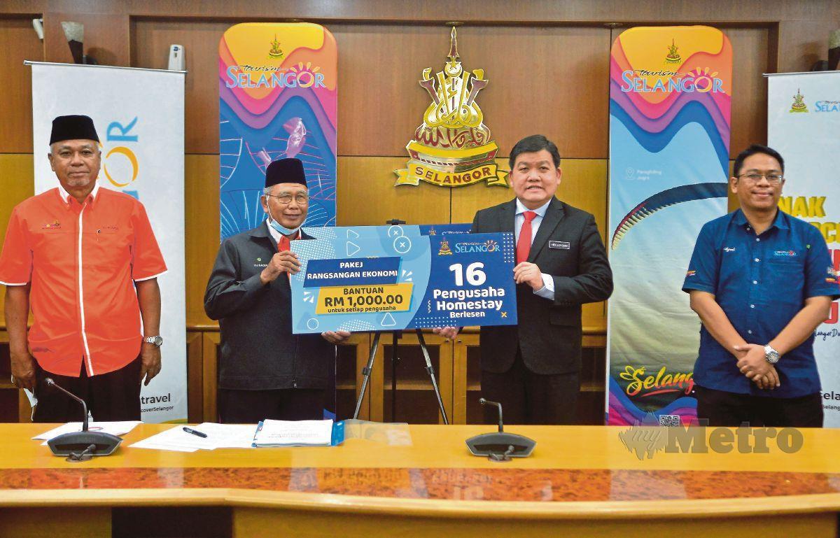 HEE (dua dari kanan) menyerahkan bantuan kepada penggiat industri pelancongan.