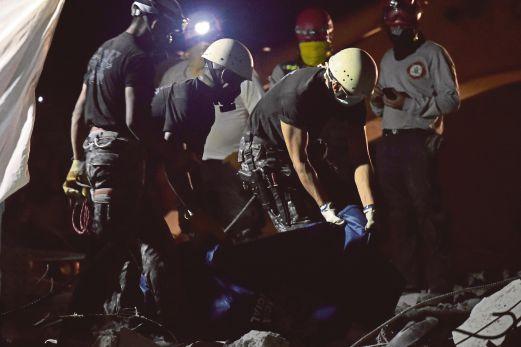 ANGGOTA penyelamat membawa mayat yang ditemui dalam runtuhan di Pedernales, Ecuador.