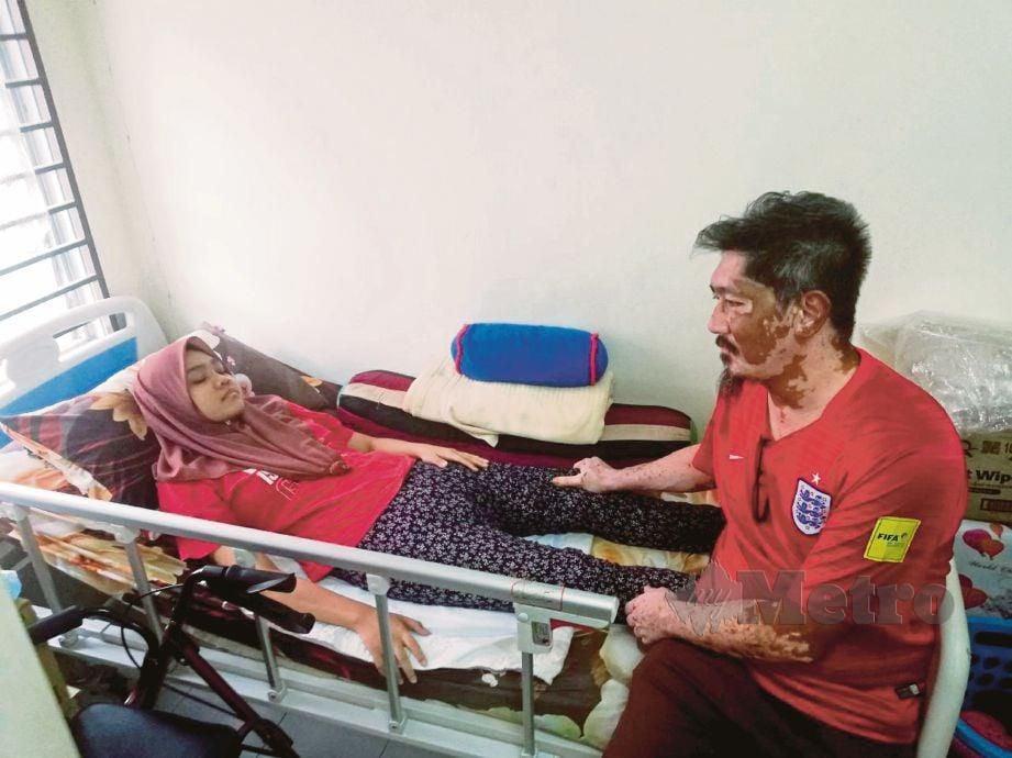 FAHAIZAL Zee bersama Nurul Sharmine Sofea yang terlantar di atas katil berikutan lumpuh separuh badan.
