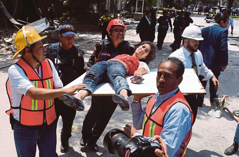 ANGGOTA penyelamat membawa seorang wanita yang cedera selepas terperangkap di celah runtuhan. - AFP