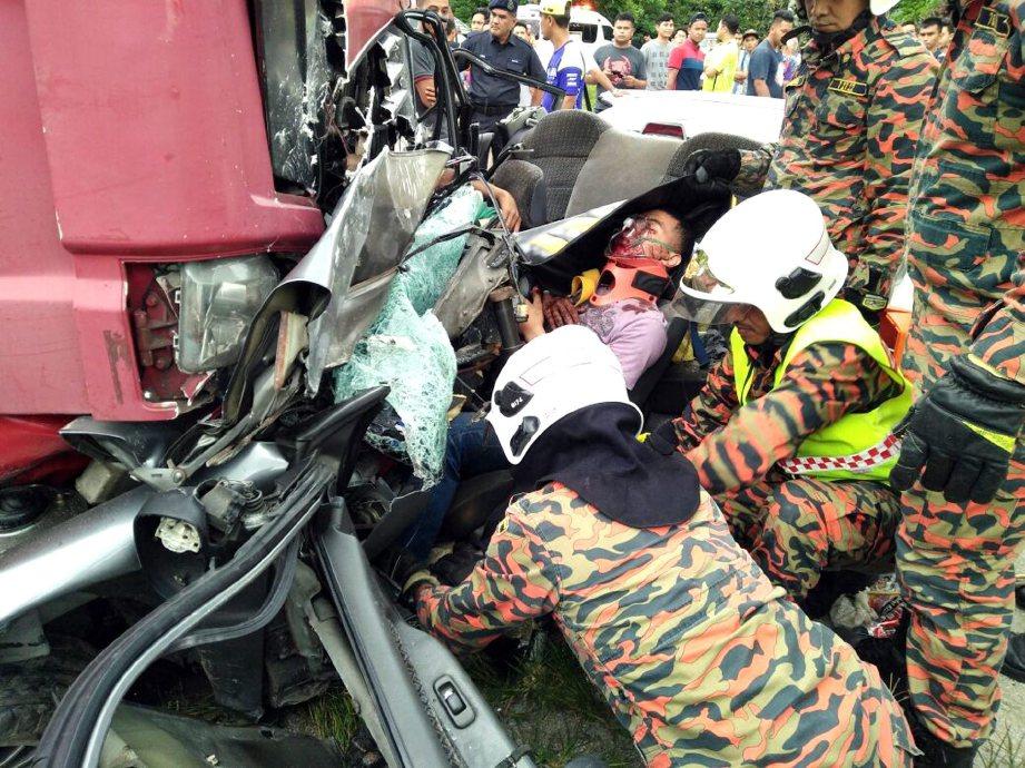 ANGGOTA bomba berusaha mengeluarkan Rohid yang cedera parah di Kilometer 12, Jalan Lipis-Merapoh.