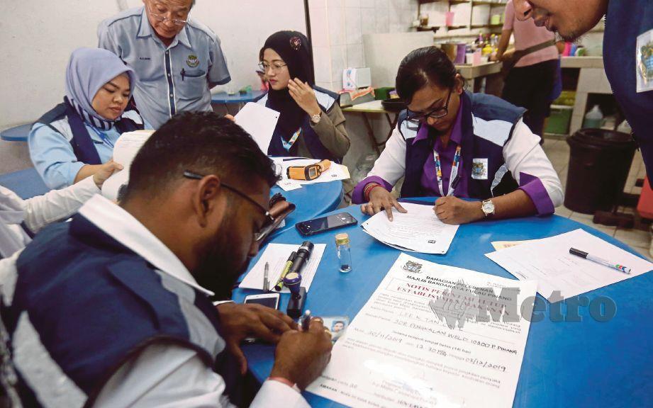 PASUKAN pegawai kesihatan membuat laporan selepas melakukan pemeriksaan di sebuah restoran. FOTO Danial Saad