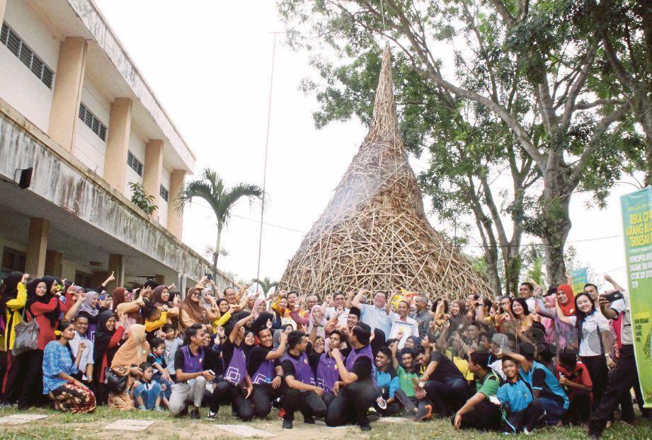 PELAJAR dan guru SMK Seri Kampar bersama replika sarang burung tempua yang dibina.