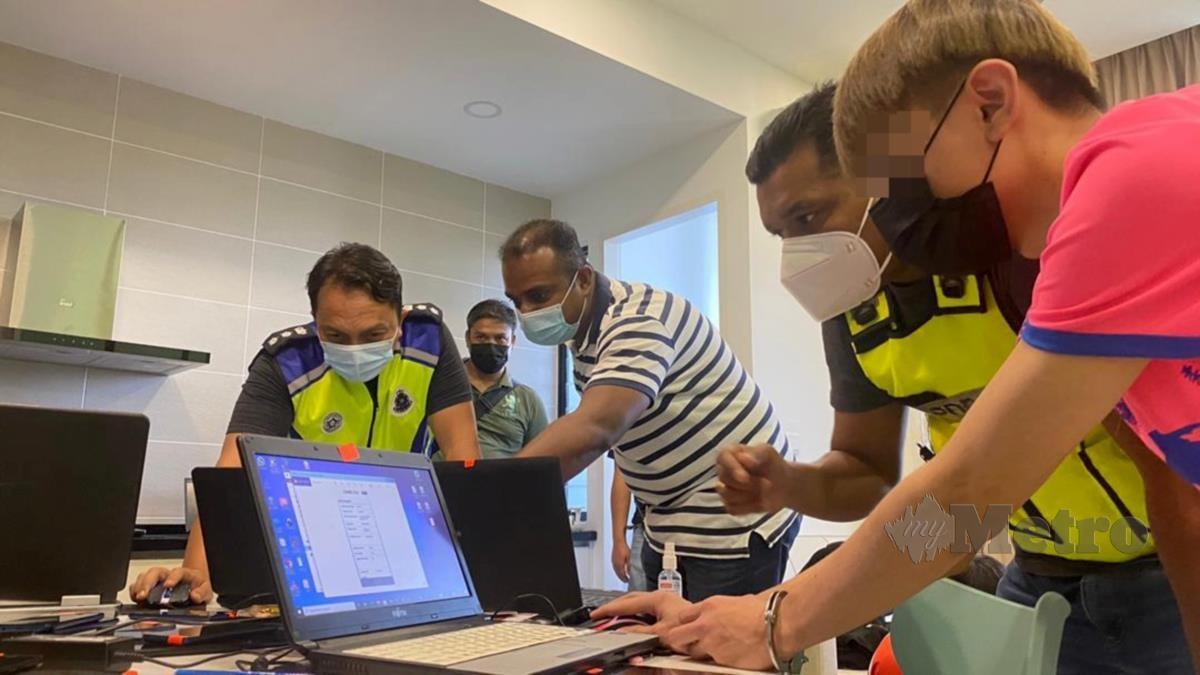 DZULKHAIRI (kiri) melihat laman web digunakan anggota sindiket. FOTO Hazri A Bakar