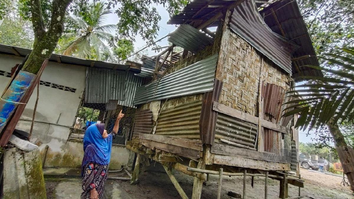 AZIZAH menunjukkan atap rumahnya yang musnah dilanda ribut di Kampung Tasek Bakong. FOTO Syaherah Mustafa