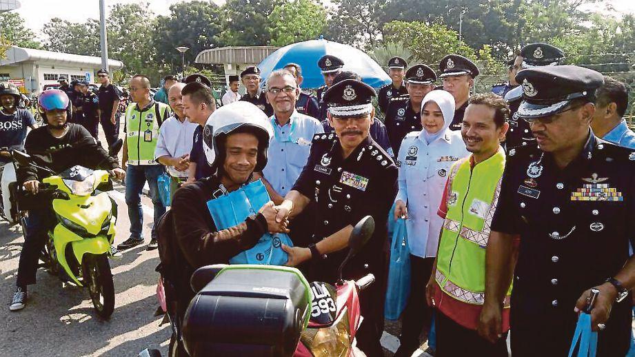 OTHMAN menyerahkan pek sumbangan kepada penunggang motosikal di Tol Simpang Balak, semalam.