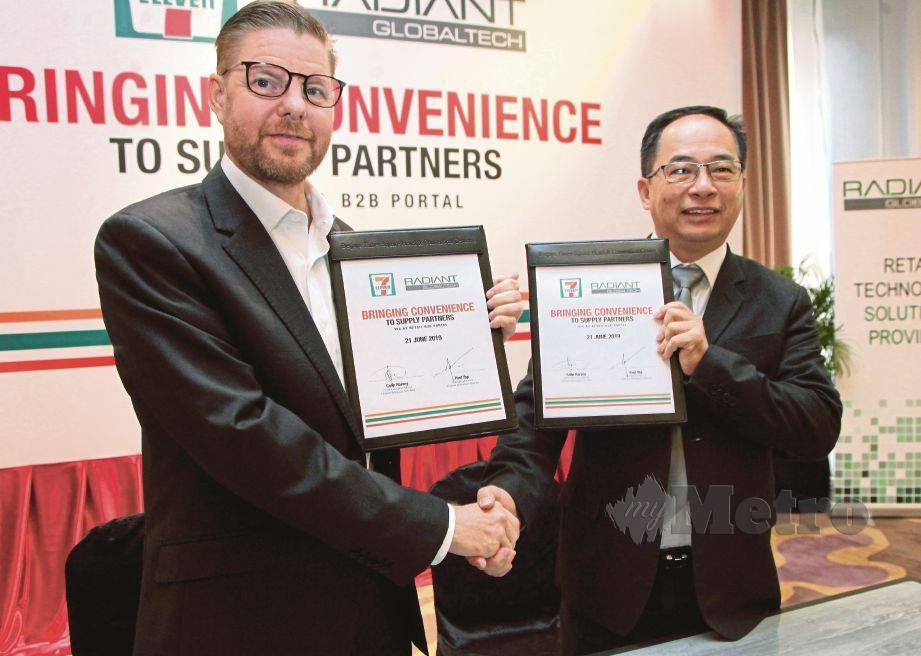 COLIN (kiri) bertukar dokumen dengan Pengarah Urusan Radiant Globaltech, Paul Yap Ban Foo, semalam. FOTO Nik Hariff Hassan