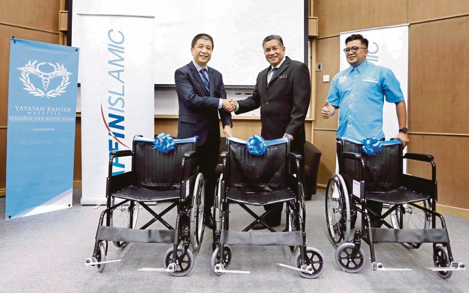 DARI kiri, Ferdaus menyerahkan kerusi roda kepada Mohd Isa disaksikan Pengasas Yayasan Kanser Malaysia, Mohd Royzilee Mustaffa.