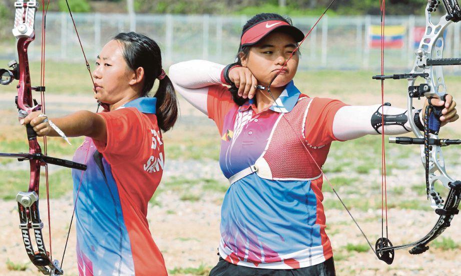 ESTHER Yong (kiri) dan  Yee Ting ketika menjalani latihan di Lapang Sasar Memanah UNIMAS.