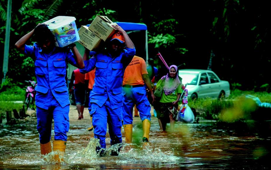 ANGGOTA penyelamat membantu membawa pulang barang bantuan milik mangsa banjir.