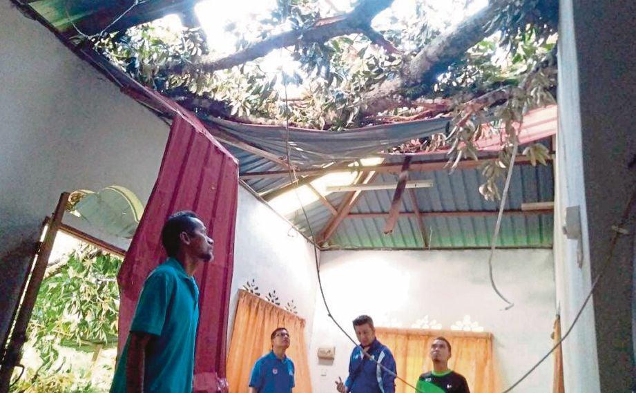 ABD Rahman (kiri) melihat bumbung rumahnya yang dihempap pokok durian.