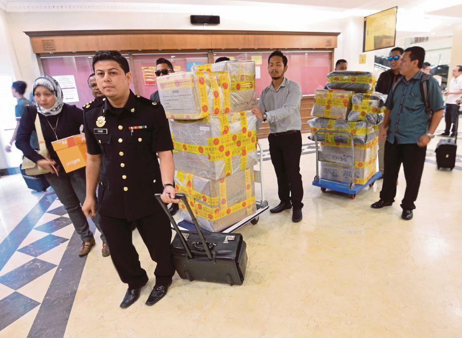 PEGAWAI SPRM membawa sebahagian barang kes ke mahkamah, semalam.