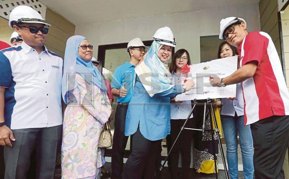 RINA  (dua dari kiri) bersama Ahmad Faizal  menandatangani plak perasmian tapak Tabika KEMAS Desa Harapan di Kampung Kinjang, Chenderiang.