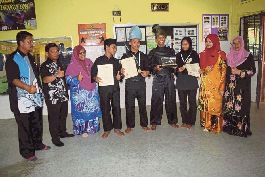 PESILAT kebanggaan SMK Chukai bersama pingat yang dimenangi.