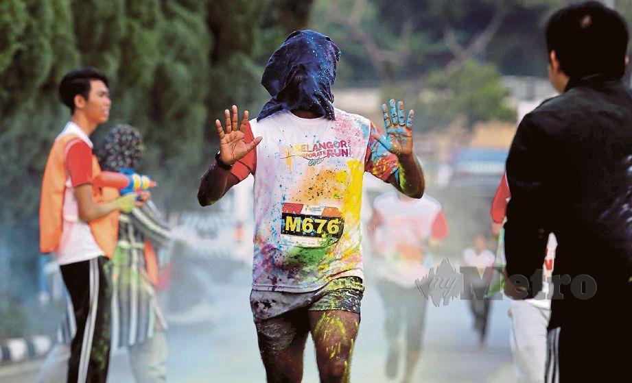 PAKAIAN seorang peserta dipenuhi serbuk warna-warni.