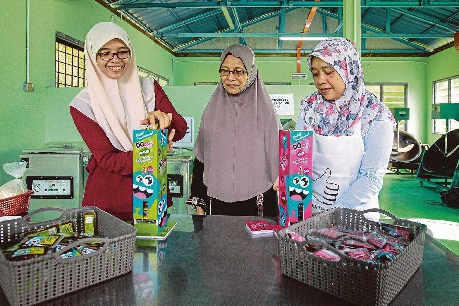 DODOL tradisional diusahakan tiga beranak (dari kiri) Siti Noor Iliyani, Nor'aini dan Siti Aminah yang dijenamakan semula.