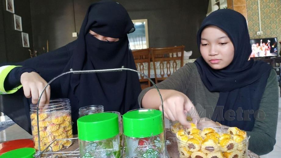AINUR Aisha (kanan) bersama Ainur Khatijah menyusun kuih raya. FOTO Ahmad Rabiul Zulkifli