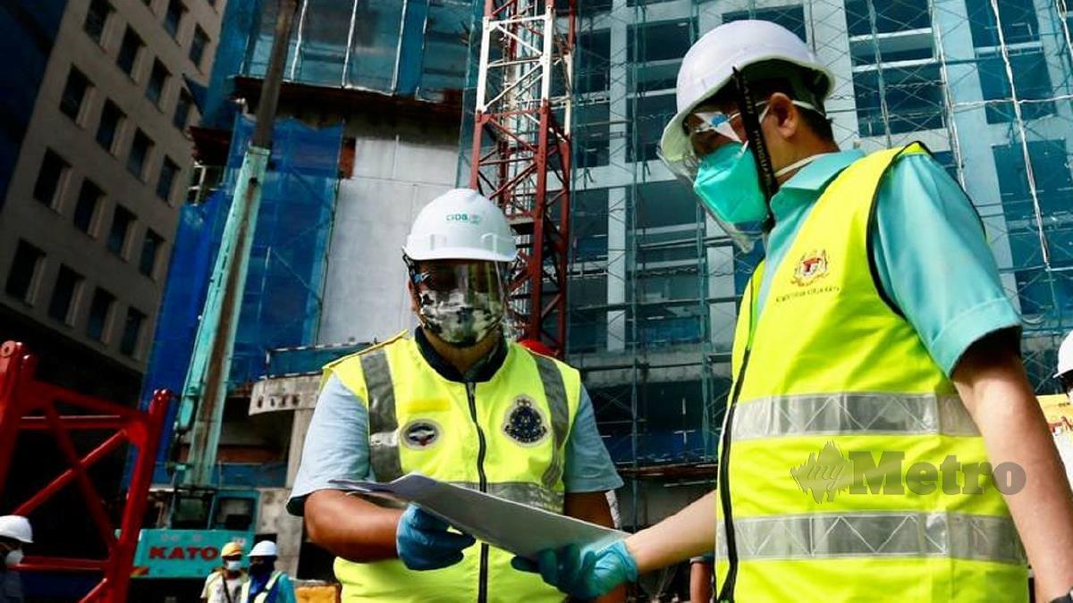 FADILLAH (kiri) membuat lawatan ke tapak bina di Kuala Lumpur bagi memantau tahap pematuhan prosedur operasi standard (SOP). FOTO Fathil Asri
