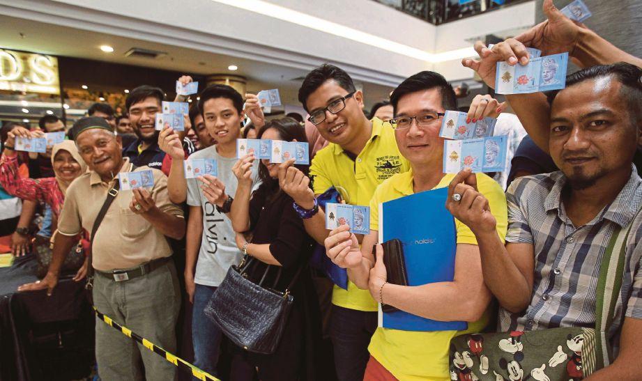 ORANG ramai menunjukkan duit pendahuluan RM1 .