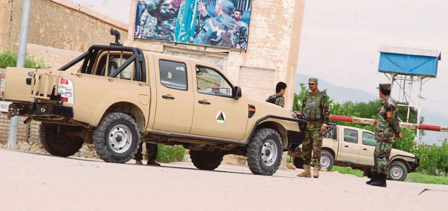 PASUKAN keselamatan Afghanistan berkawal di luar kem tentera di Mazar-i-Shariff selepas serangan kelmarin. - EPA