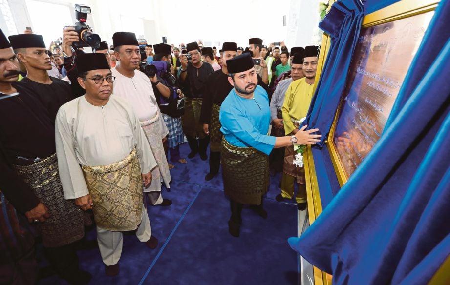 Tunku Ismail   menarik tirai sebagai gimik perasmian sambil diperhatikan Mohamed Khaled   (kiri) pada  majlis Perasmian Masjid Bandar Seri Alam, Pasir Gudang, semalam.