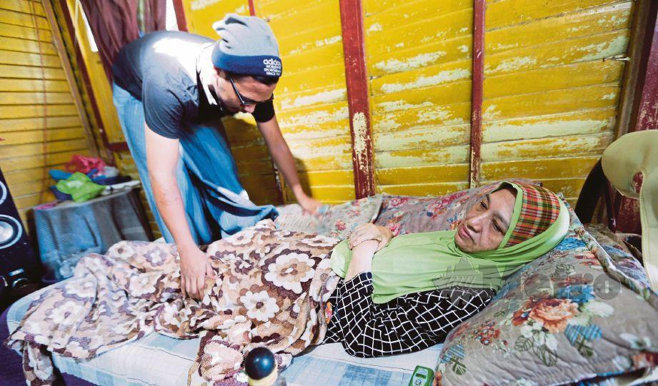 MOHAMAD Adam  menjaga ibunya yang terlantar lumpuh sebelah tubuh selepas diserang angin ahmar  di rumahnya di Kampung Laut 1, Tumpat.