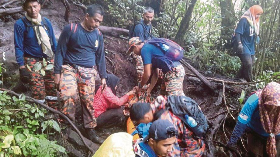 ANGGOTA bomba membawa turun seorang wanita yang cedera di belakang badan selepas terjatuh terkena batu ketika mendaki Gunung Irau.