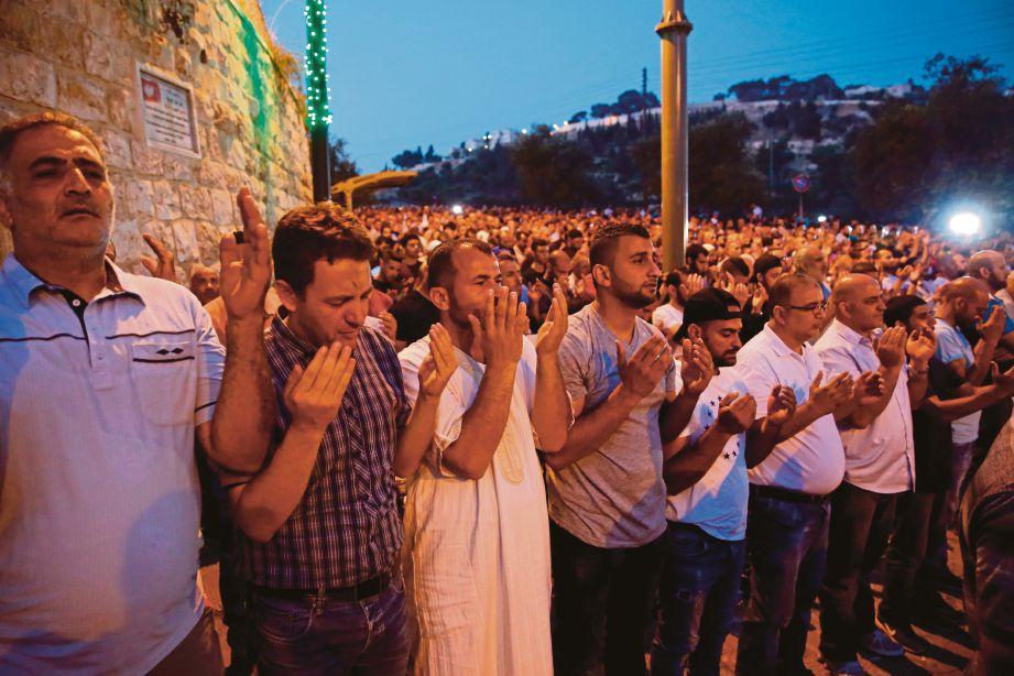 PENDUDUK Palestin berdoa selepas bersolat  di hadapan pintu masuk Al-Aqsa malam kelmarin.  - AFP