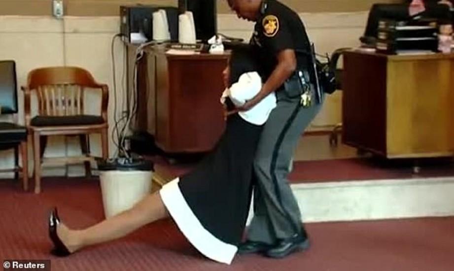 PEGAWAI mahkamah terpaksa mengheret Tracie keluar. FOTO Agensi