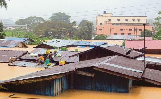 DUA lelaki menyelamatkan diri ke atas bumbung  apabila rumah dinaiki air di Bandar Lama Gua Musang.