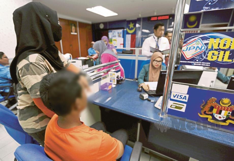 UMRAH, 34,   menemani anaknya membuat kad pengenalan di Pejabat Pendaftaran Negara, Masjid Tanah.