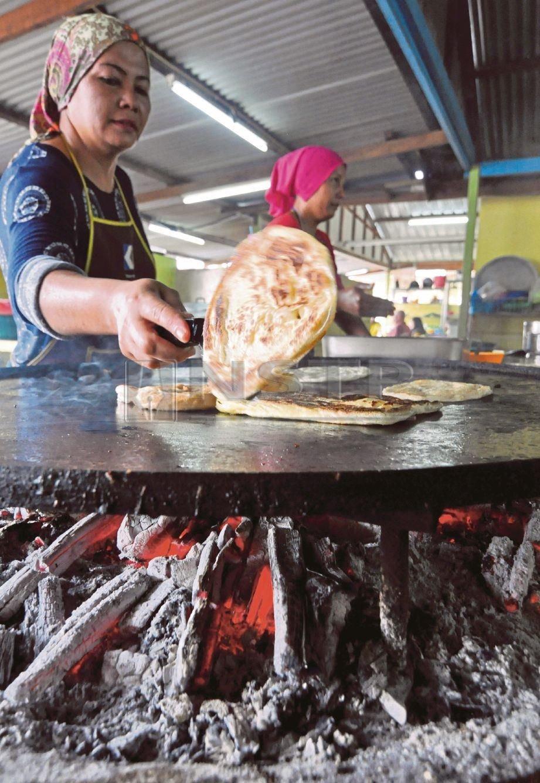 SITI Ida  menyediakan roti canai menggunakan dapur   kayu   untuk dinikmati pelanggannya di kedai Roti Canai Kayu Arang.