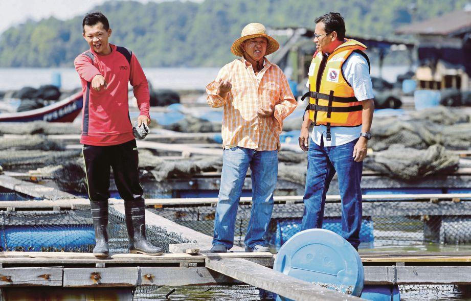 AHMAD Shabery (kanan) melihat sangkar ikan yang rosak akibat dipukul ribut di Pulau Aman dalam lawatan kerja sehari di Pulau Pinang.