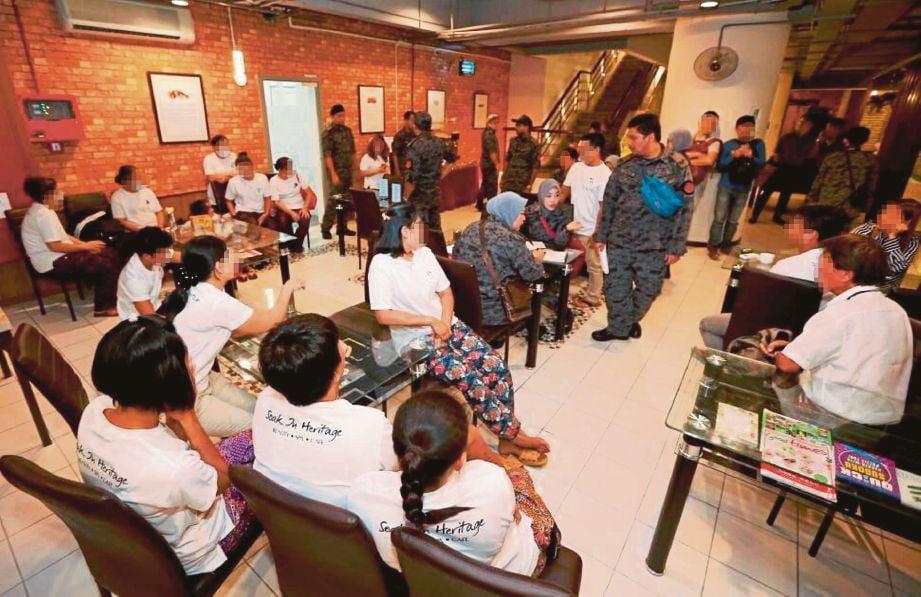 Pegawai imigresen membuat pemeriksaan  ketika serbuan di spa di Jalan Sultan Ahmad Shah,  kelmarin.